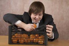 Il giovane tiene un mandarino Fotografie Stock Libere da Diritti