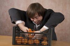 Il giovane tiene un mandarino Immagini Stock Libere da Diritti