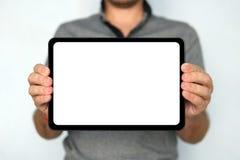 Il giovane tiene una compressa del cuscinetto di tocco su fondo bianco isolato La grande compressa digitale con lo schermo bianco immagine stock