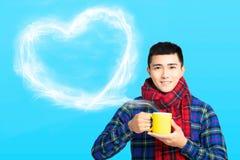 il giovane tiene una tazza con caffè o tè caldo fotografie stock libere da diritti