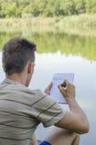 Il giovane tipo annota in un taccuino fotografia stock libera da diritti
