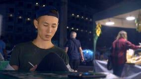 Il giovane tipo asiatico bello fuma la sigaretta sulla via nella sera contro il contesto di una via occupata della città, sfuocat video d archivio