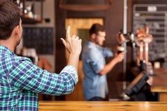 Il giovane tipo attraente ordina la lager in pub Fotografia Stock