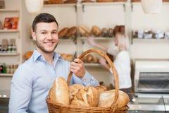 Il giovane tipo attraente sta acquistando il pane fresco fotografia stock libera da diritti