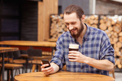 Il giovane tipo attraente sta utilizzando il telefono dentro Immagine Stock
