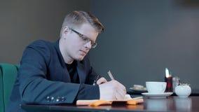 Il giovane tipo bello sta prendendo le note, sedentesi alla tavola in caffetteria video d archivio