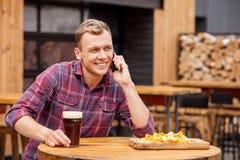 Il giovane tipo bello sta utilizzando il telefono nella barra Fotografie Stock