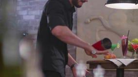Il giovane tipo che il barista manipola con un agitatore prepara per gli amici un bello e cocktail saporito 03 video d archivio