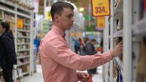 Il giovane tipo compra i chicchi di caffè in un deposito o in un supermercato video d archivio