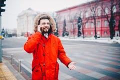 Il giovane tipo con la barba ed il rivestimento rosso in cappuccio uno studente utilizza il telefono cellulare, tiene in sua mano fotografia stock libera da diritti
