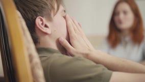 Il giovane tipo del ritratto ad una sessione con uno psicoterapeuta l'adolescente parla dei suoi problemi e timori al stock footage