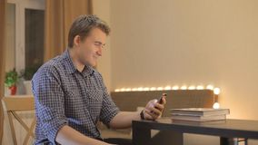 Il giovane tipo guarda nelle notizie del telefono video d archivio