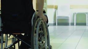 Il giovane tipo guida tramite un corridoio dell'ospedale su una sedia a rotelle stock footage