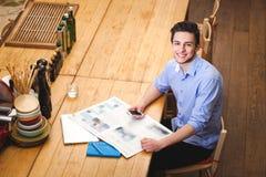Il giovane tipo ha letto un telefono della tenuta e del giornale nello styl italiano Fotografie Stock