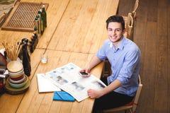 Il giovane tipo ha letto un telefono della tenuta e del giornale nello styl italiano Immagine Stock