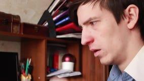 Il giovane tipo ha un naso semiliquido, pulisce il suo naso con un fazzoletto, starnutisce nel suo fazzoletto stock footage
