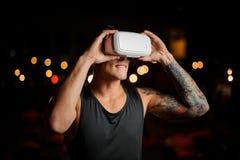 Il giovane tipo morde il suo labbro in vetri di realtà virtuale contro Immagini Stock