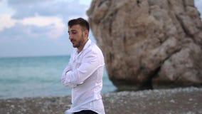 Il giovane tipo pensieroso cammina lungo la spiaggia L'uomo barbuto bello passa il tempo nel pensiero all'aperto cyprus Pafo stock footage
