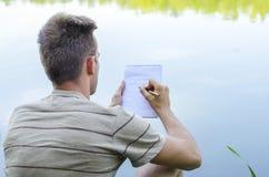 Il giovane tipo scrive in un taccuino fotografia stock libera da diritti