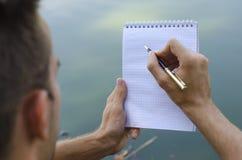 Il giovane tipo scrive in un taccuino fotografie stock