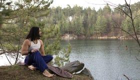Il giovane tipo si siede sull'alta banca sopra il lago Fotografia Stock Libera da Diritti