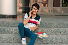 Il giovane tipo sorridente si siede su una via con i libri e sulla conversazione sul telefono Immagine Stock