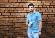 Il giovane tipo sta bevendo il caffè, contro un muro di mattoni, vestito in vestiti dell'estate, fondo urbano, stile libero fotografie stock libere da diritti