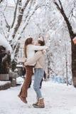 Il giovane tipo tiene una bella ragazza nelle sue armi Coppie in maglioni fotografie stock