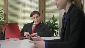 Il giovane tipo in un vestito si siede nell'ufficio, in un dialogo ed in una donna secondaria Flirtando con la ragazza Lavoro nel archivi video