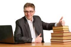 Il giovane tirante che lavora ad un computer portatile mostra un gesto del pollice in su per dire la t Fotografia Stock Libera da Diritti