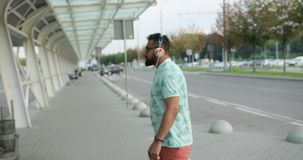 Il giovane turista africano attraente nei heaphones sta camminando all'aeroporto per un volo Sta tirando il suo bagaglio 4K stock footage