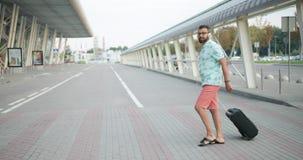 Il giovane turista africano bello in maglietta, shorts e cuffie sta tirando il suo bagaglio mentre camminava verso l'aeroporto video d archivio