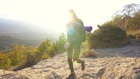 Il giovane turista con uno zaino scala la montagna e solleva le sue mani su con la gioia archivi video