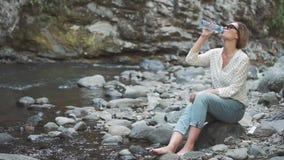 Il giovane turista grazioso sulla pietra vicino al fiume della montagna e beve l'acqua cristallina pulita a partire dalle molle d video d archivio