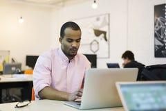 Il giovane ufficio coworking dello studente e dell'insegnante facendo uso del computer portatile si è collegato ad Internet senza Fotografia Stock