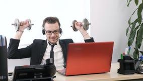 Il giovane in un vestito sta lavorando nell'ufficio e sta facendo un esercizio per le spalle con una testa di legno 60 fps archivi video