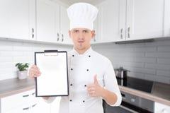 Il giovane in uniforme del cuoco unico sfoglia su e mostrando la lavagna per appunti con la c Fotografia Stock