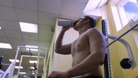 Il giovane uomo adulto beve l'acqua mentre si siede su un banco di formazione nella palestra