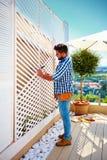 Il giovane uomo adulto che costruisce la parete di legno della pergola sul patio del tetto suddivide in zone a casa Fotografia Stock
