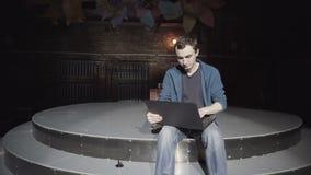 Il giovane uomo adulto lavora per il computer portatile video d archivio