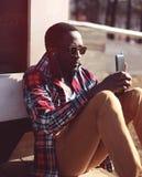 Il giovane uomo africano alla moda ascolta musica e smartphone usando, Immagini Stock