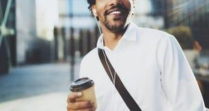 Il giovane uomo africano americano alla moda in cuffia che cammina alla città soleggiata con porta via il caffè e godere di ascol Immagine Stock