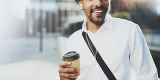 Il giovane uomo africano americano felice in cuffia che cammina alla città soleggiata con porta via il caffè e godere di ascoltar Immagine Stock