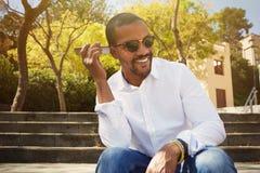 Il giovane uomo africano felice in camicia bianca ascolta messaggio sano sul telefono cellulare mentre si siede all'aperto Immagine Stock