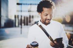 Il giovane uomo afroamericano sorridente in cuffia che cammina alla città soleggiata con porta via il caffè e per mezzo del suo t Fotografia Stock