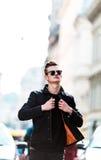 Il giovane uomo alla moda in occhiali da sole cammina giù la via Fotografia Stock