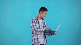 Il giovane uomo asiatico allegro con il computer portatile a disposizione impara circa la conquista sul fondo blu stock footage
