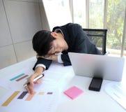 Il giovane uomo asiatico bello di affari cade addormentato sullo scrittorio funzionante immagini stock libere da diritti
