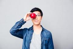 Il giovane uomo asiatico che copre il suo osserva con la mela Immagine Stock