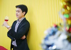 Il giovane uomo asiatico esecutivo è stante e vedente il vetro del vino rosso immagini stock
